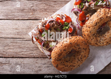 Bagels with Pulled pork, onions, cabbage and sauce on the table. horizontal view from above - Stock Photo