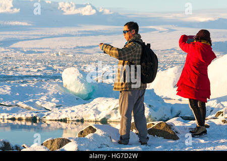 Two tourists taking photos of spectacular scenery at Jokulsarlon Glacial Lagoon, Iceland in January - Stock Photo