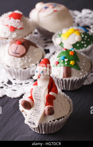 Beautiful delicious cupcakes with Christmas decorations close-up. vertical - Stock Photo