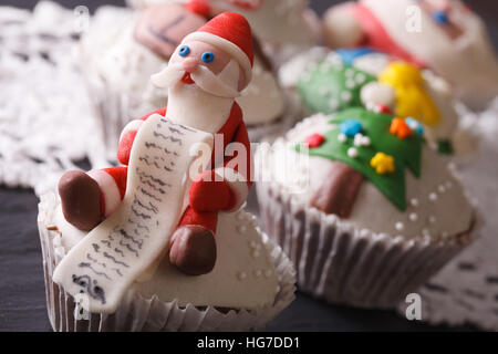 Christmas cupcakes decorated with the figure of Santa macro on the table. horizontal - Stock Photo