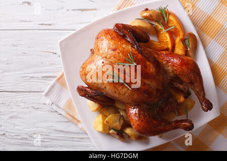 baked whole chicken with oranges and potatoes on a plate. horizontal view from above - Stock Photo