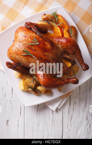 baked whole chicken with oranges and potatoes close-up on a plate. vertical top view - Stock Photo