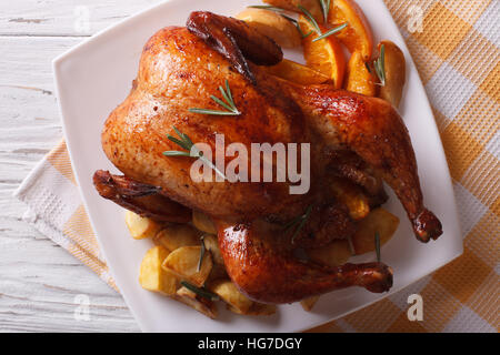 baked whole chicken with oranges and potatoes close-up on a plate. horizontal view from above - Stock Photo