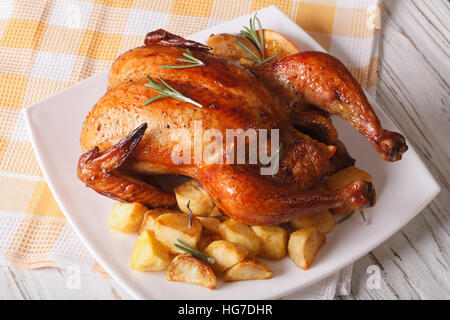 whole roast chicken with oranges and potatoes on a plate. horizontal - Stock Photo
