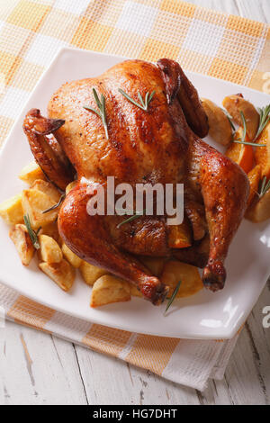 whole roast chicken with oranges, potatoes and apples close-up on a plate. Vertical - Stock Photo