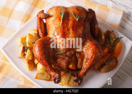 whole roast chicken with oranges, potatoes and apples close-up on a plate. horizontal - Stock Photo