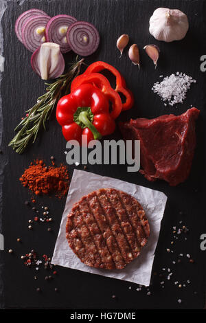 Raw Ground beef meat Burger steak cutlets with ingredients on the board. vertical view from above - Stock Photo