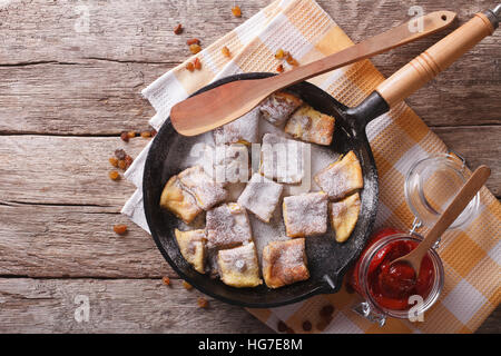 Delicious omelette Kaiserschmarrn with plum sauce on a frying pan. horizontal top view - Stock Photo
