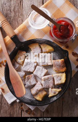 Delicious omelette Kaiserschmarrn with plum sauce close-up on a frying pan. vertical top view - Stock Photo