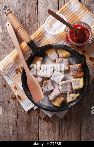 Delicious omelette Kaiserschmarrn with plum sauce on a frying pan. vertical top view - Stock Photo