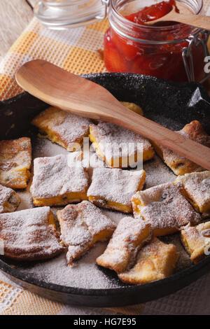 sweet Kaiserschmarrn with plum sauce closeup on a frying pan. vertical - Stock Photo