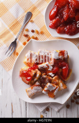 Delicious omelette Kaiserschmarrn with plum sauce close-up on a plate. vertical top view - Stock Photo