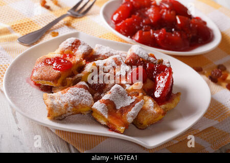 Austrian omelette Kaiserschmarrn with plum sauce close-up on a plate. horizontal - Stock Photo