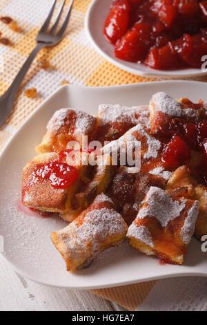 Austrian dessert Kaiserschmarrn with plum sauce close-up on a plate. Vertical - Stock Photo