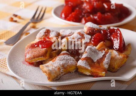 Austrian dessert Kaiserschmarrn with plum sauce close-up on a plate. horizontal - Stock Photo