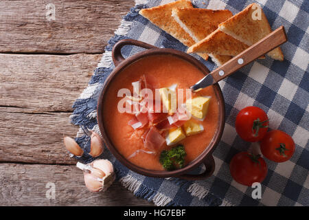 Salmorejo soup with ham and eggs in a bowl on the table. horizontal view from above - Stock Photo