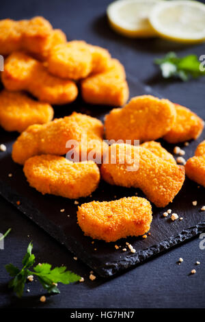 Bunch of tasty chicken nuggets on a slate plate - Stock Photo