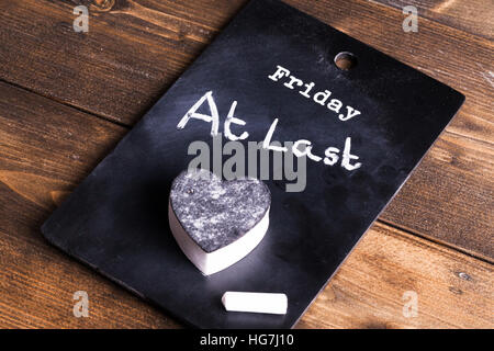 Friday at last, notice on a chalk board with chalk and heart shaped eraser. Concept of working people pleased to - Stock Photo