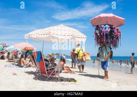 RIO DE JANEIRO - JANUARY 05, 2016: Beach vendors and sunbathers share a bright day on Ipanema Beach. - Stock Photo