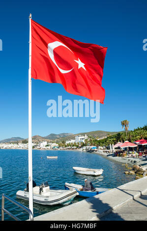 Turkish flag flying in bright blue sky in Bodrum, Turkey - Stock Photo