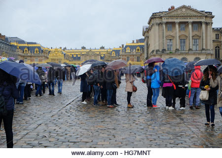 People with umbrellas wait in line to enter the Palace of Versailles on a rainy morning. - Stock Photo