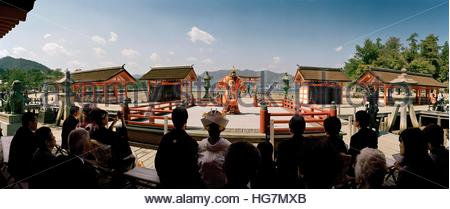 On Miyajima, attendees to a wedding watch a Buraku dance with the iconic torii in the background. - Stock Photo