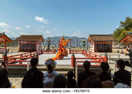 On Miyajima, wedding attendees watch a Buraku dance with the iconic torii in the background. - Stock Photo