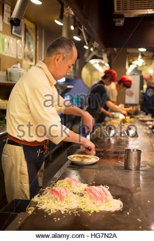 Chefs in a restaurant prepare okonomiyaki, a savory stuffed pancake. - Stock Photo