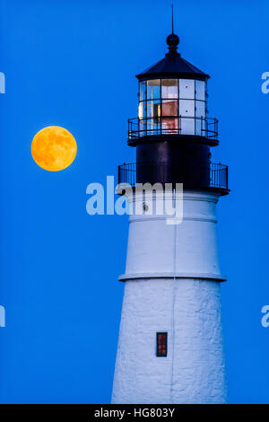 Super Moon rising over the lighthouse at Portland Head in Cape Elizabeth, Maine, USA. - Stock Photo