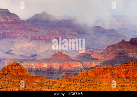 Snow showers over the Grand Canyon as sunset lights a ridge, as seen from Yavapai Point. Grand Canyon National Park, - Stock Photo