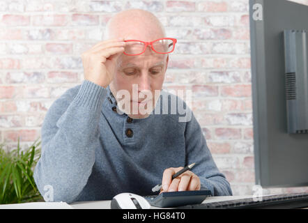 mature businessman having eyesight problems, he is using calculator - Stock Photo