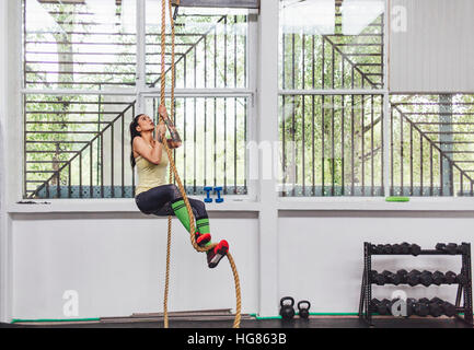 Athlete climbing rope in gym - Stock Photo
