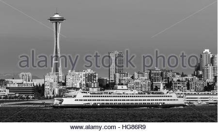 A Washington State Ferry crosses in front of the iconic Space Needle on Elliott Bay in Seattle - Stock Photo