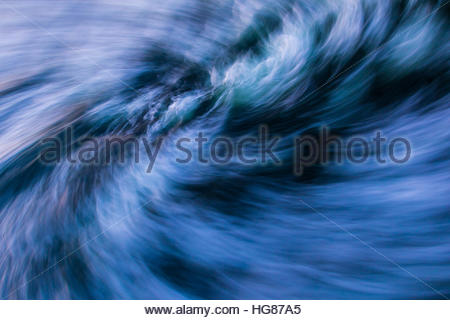Ocean waves are blurred into a churning vortex in this abstract image - Stock Photo