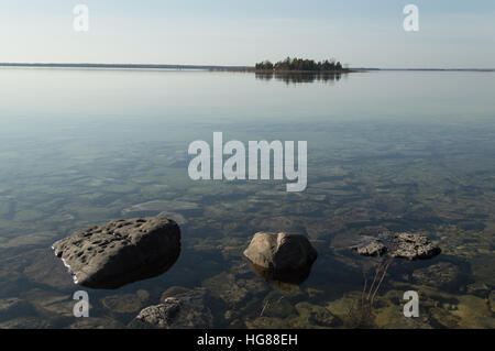 Dead calm image of shallow, clear lake huron water and limestone rocks with small tree-covered island on the horizon - Stock Photo