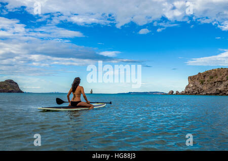 Woman sitting on paddleboard in sea against blue sky - Stock Photo