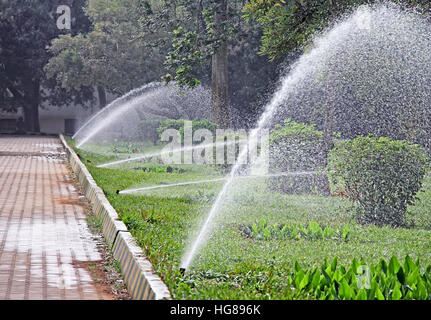 Several working water sprinklers in a row irrigating park garden - Stock Photo