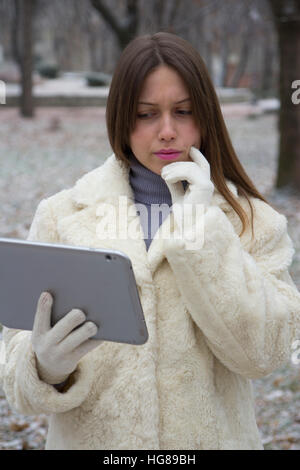 young girl in the park looking at tablet - Stock Photo