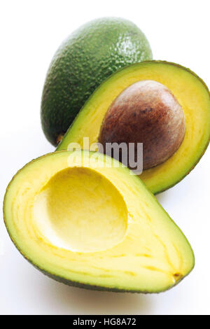 Avocados (Persea americana), whole and halved - Stock Photo