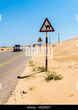 Street through sandy desert with sign warning of camel crossings, Ash Sharqiyah South, Oman - Stock Photo