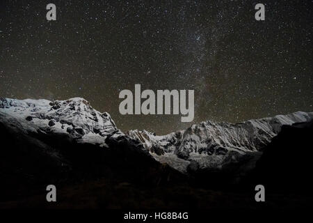 View of the snow covered Annapurna 1 North Face, mid, and the Annapurna South summit , left at night with stars - Stock Photo