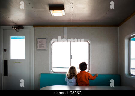 Rear view of siblings looking through window while traveling in ferry - Stock Photo