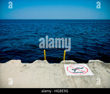 No swimming sign on pier over sea against clear blue sky - Stock Photo