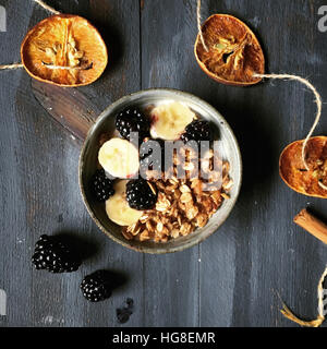 Overhead view of granola with fruits in bowl by garland on wooden table - Stock Photo