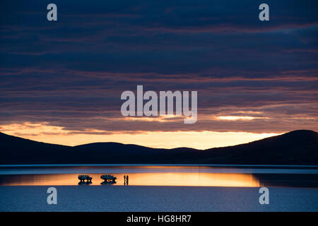 2 cars and some people stopped on a reflective lake during sunset with mountains - Stock Photo
