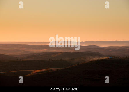 A car drives along a mountain ridge in the distance during sunset - Stock Photo