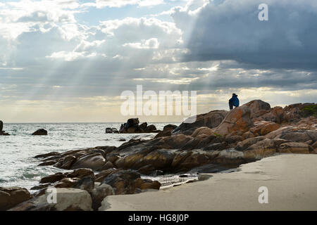 A man sits on rocks on a beach looking at the ocean with gods rays sunlight shining through clouds - Stock Photo