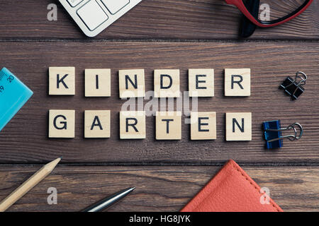 Office stuff and Kinder Garden phrase collected with letters on wooden surface - Stock Photo