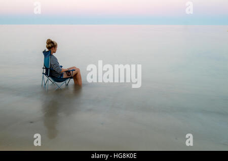 teenage girl relaxing sitting in deck chair in the sea - Stock Photo