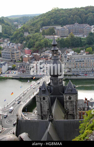 View of the top of Church of Our Lady in Dinant Belgium with the River Meuse and the bridge joining two halves of - Stock Photo